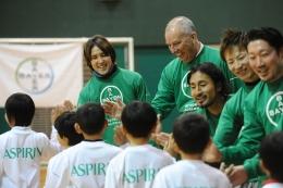 子どもらとハイタッチする細貝選手(左)。隣はハンスディーター・ハウスナー日本バイエル社長。