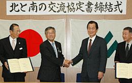 締結式で握手を交わすJA南さつまの下野組合長(中央左)とJA津軽みらいの阿保組合長(中央右)