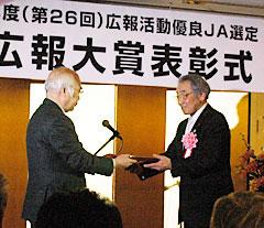 萬歳会長から表彰を受ける柴原組合長(右)