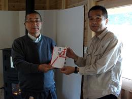 5月9日、南三陸町で行われた贈呈式で。鈴江茂敏・地域再生コミュニティビジネス推進協会理事(左)から山内正文・南三陸福興まちづくり機構理事長へ目録が手渡された。