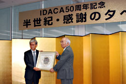 ICA-APから記念の楯を贈られる萬歳章理事長(右)