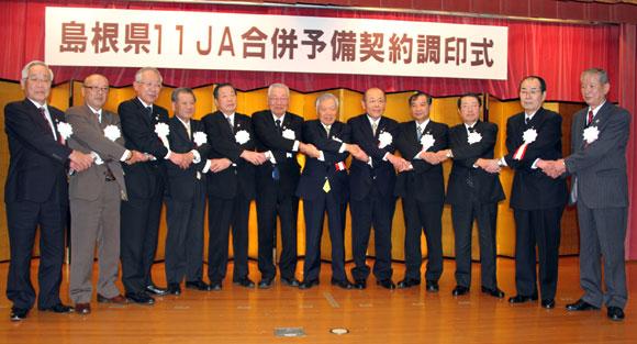 平成27年3月の「1県1JA」をめざし予備契約調印式に臨む萬代会長(中央)と11JA組合長ら