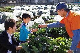 利用者に野菜作りをアドバイスする菜園アドバイザー(右)