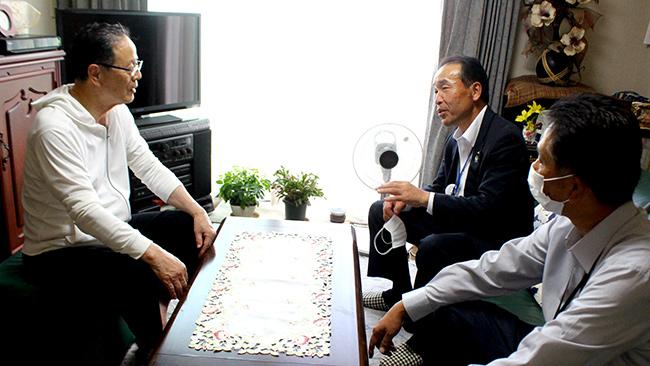 農家を訪問し、話を聞く小島組合長(右奥)