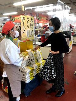 「贅沢あきろまん」発売当日、店頭で説明を受ける買い物客(広島市安佐南区で)