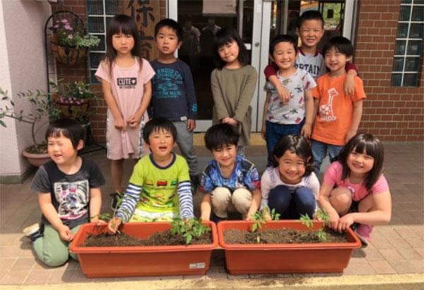 笑顔で中玉トマト苗を受け取る園児たち