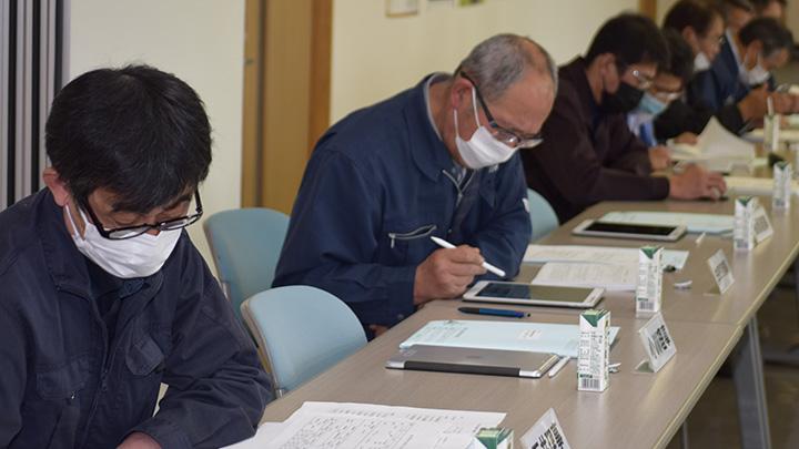 タブレットにアップされた資料に目を通す理事会の参加者
