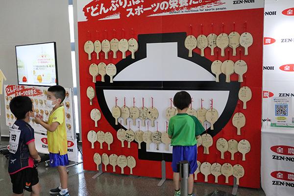 卓球ニッポンへの応援メッセージを綴る絵馬の展示に参加する選手たち
