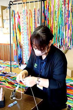 万羽鶴プロジェクトで集まった折鶴に紐を通す職員