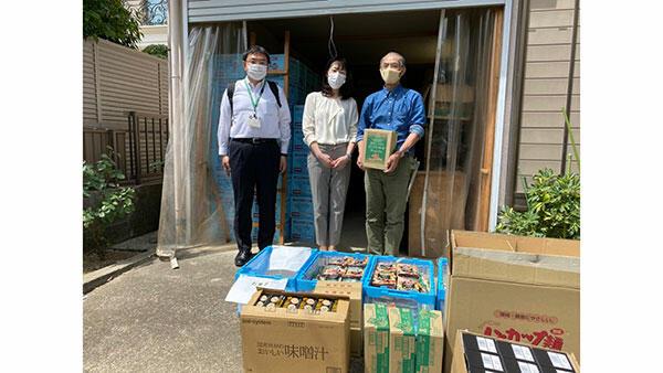 飲料やカップめんを提供する藤田理事長(中)
