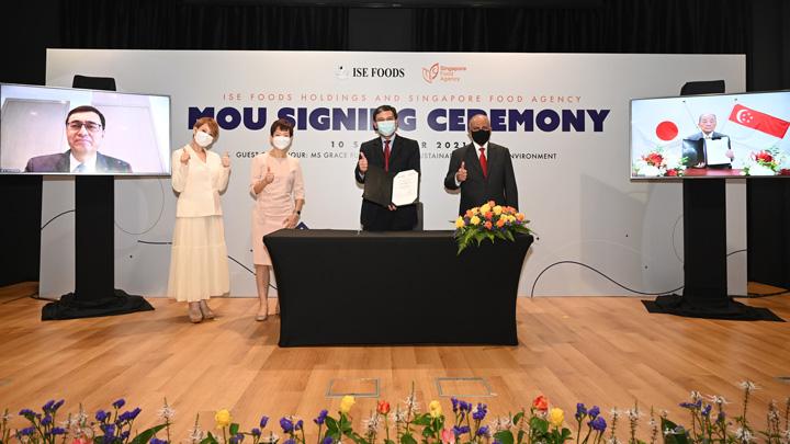 """シンガポールの鶏卵農場開発に関するMOU調印式。左から山崎駐シンガポール日本国特命全権大使(Zoom)、IFH吉川月乃CEO、グレース・フー大臣、リムSFA最高経営責任者、チャンドラ・ダスIFH取締役、イセ食品の伊勢名誉顧問兼オーナー(Zoom)"""""""