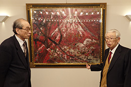 趣味で集めた絵画の前の新田会長(右)と谷口教授(平田牧場本社で。数多くの名作があり、自由に鑑賞できる)