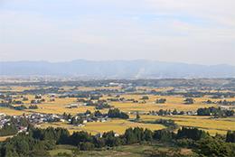 置賜平野の散居集落(飯豊町)。イギリスの女性旅行家イザべラ・バード(1831〜1904年)は、明治時代の東北地方を旅行し「日本奥地紀行」を書いた。そのなかで置賜地方を「エデンの園」とし、その風景を「東洋のアルカディア」(古代ギリシャの伝承上の理想郷)」と評した。飯豊町の「散居」風景は平成5年の「第1回美しい日本のむら経験コンテスト」最高賞の農水大臣賞を受賞した。(写真は飯豊町提供)