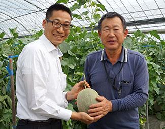 肥後グリーンのほ場を取材する仕入れ担当の八尾氏(左)と生産者の大江田さん(2018年当時)